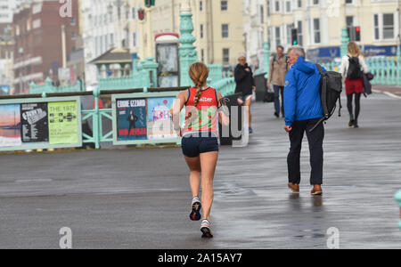 Brighton, UK. 24th Sep, 2019. A runner braves the conditions on Brighton seafront as wind and rain batters most of Britain today. Credit: Simon Dack/Alamy Live News - Stock Photo