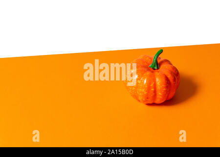 Bright ripe pumpkin with a ponytail on an orange-white background with place for text - Stock Photo