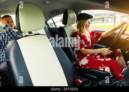 Photo of female driver driving and male passenger riding in car during day - Stock Photo