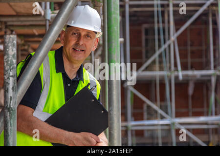 Male builder foreman, construction worker, engineer, surveyor or site manager holding a clipboard, wearing a white hard hat and hi vis vest standing o - Stock Photo