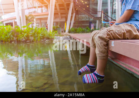 Little kids look at the water and feeding fishs on the wooden bridge.  High resolution image gallery.