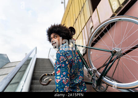 Stylish man carrying bicycle on escalator