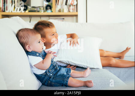 Two boys sitting on sofa and watching television at home - Stock Photo
