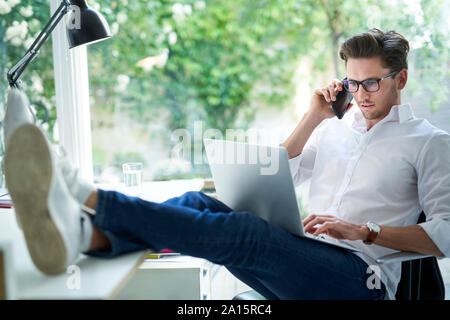 Businessman on the phone using laptop in office - Stock Photo