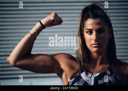 Portrait of confident young woman flexing muscles