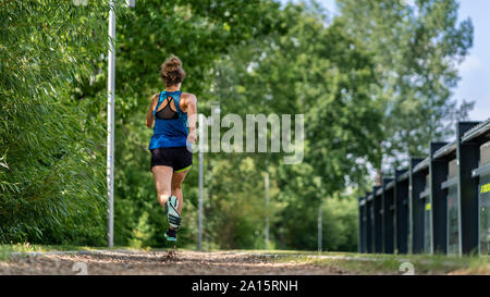 Young woman jogging on a woodchip trail