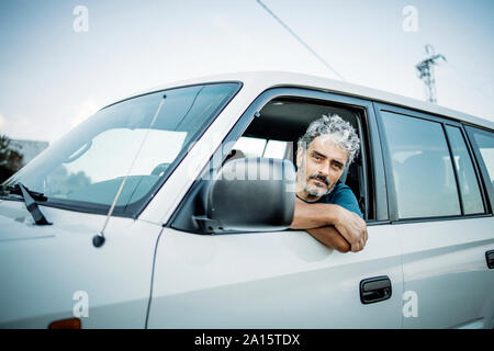 Mature man sitting in his off-road vehicle - Stock Photo