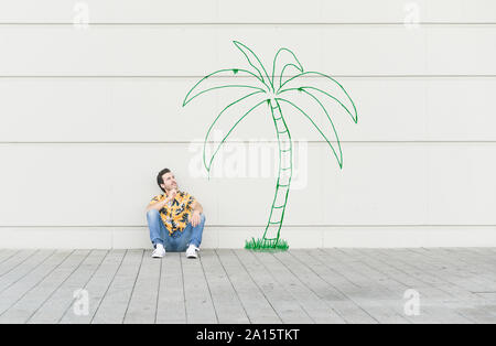Digital composite of young man sitting at a palm at a wall - Stock Photo