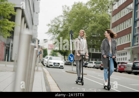 Young women riding electric scooters in the street - Stock Photo