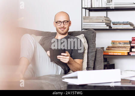 Man sitting at home on a couch using digital tablet - Stock Photo