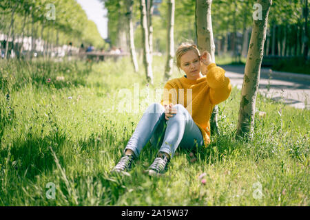 Portrait of pensive young woman sitting on a meadow looking at distance
