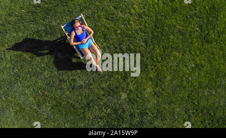 Aerial view of a young woman sunbathing on lawn - Stock Photo