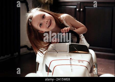 Cute little girl driving her toy car - Stock Photo