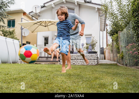 Father and son playing football in garden - Stock Photo