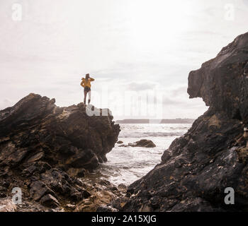 Woman wearing yellow rain jacket standing on rock - Stock Photo