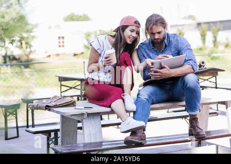Young couple sitting on table in a beer garden using tablet
