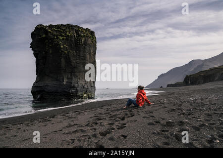 Woman on lava beach in South East Iceland, looking at the sea Stock Photo