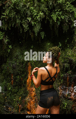 Sportive young woman with braids in forest - Stock Photo