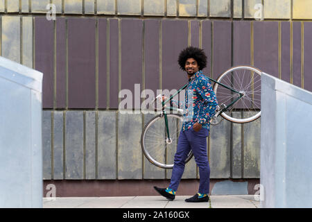 Stylish man carrying bicycle in the city