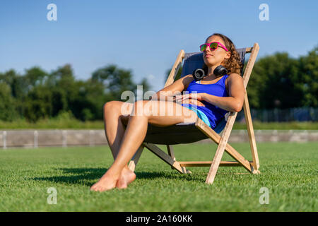 Young woman sunbathing on lawn - Stock Photo