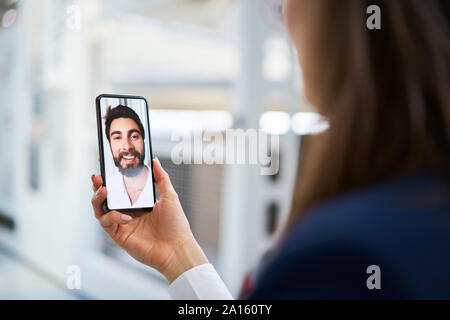 Close-up of businesswoman using smartphone chatting with colleague in factory - Stock Photo