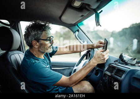 Mature man sitting sitting in his off-road vehicle checking his smartphone - Stock Photo