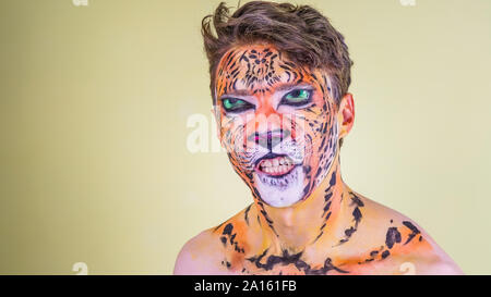 The guy with the painted face of a tiger on a bright background - Stock Photo