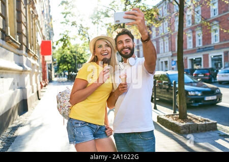 Happy young couple taking a selfie while eating ice cream in the city - Stock Photo