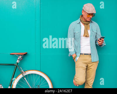 Man with Fixie bike standing in front of green wall looking at cell phone - Stock Photo