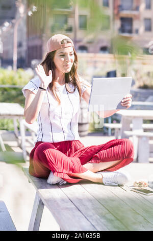 Young woman sitting on table in a beer garden using tablet - Stock Photo