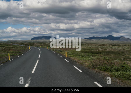 Empty road through landscape in Iceland - Stock Photo