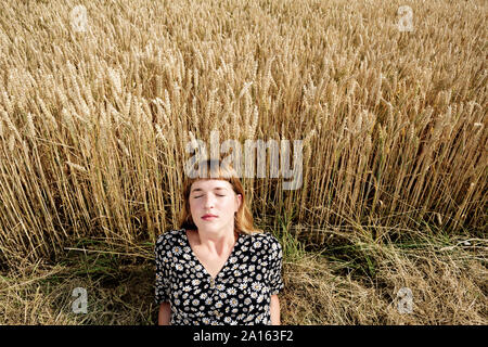 Portrait of young woman with eyes closed relaxing in front of grain field - Stock Photo