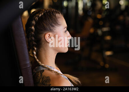 Young woman exercising in fitness gym - Stock Photo