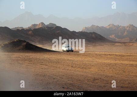 Off-road vehicle on dust in desert against sky during sunset - Stock Photo