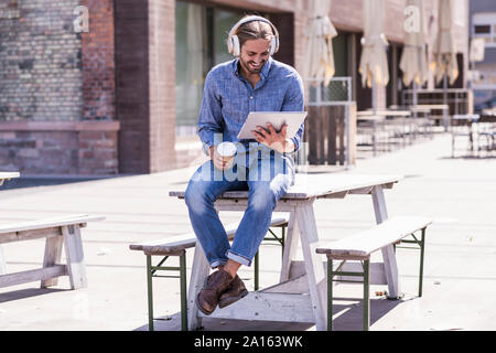Young man sitting on table in a beer garden with headphones and tablet - Stock Photo