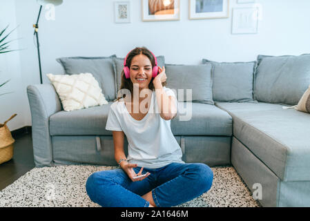 Happy young woman sitting on floor in living room listening to music with cell phone - Stock Photo