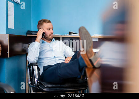 Businessman on cell phone in office - Stock Photo