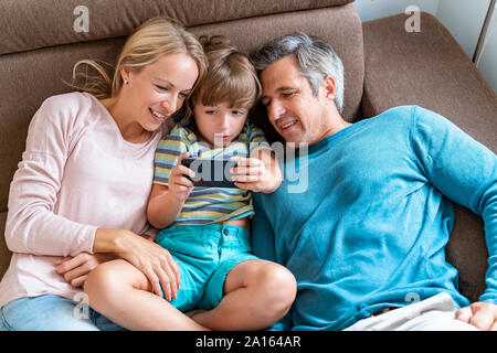 Father, mother and son using cell phone on couch at home