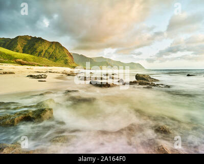 Scenic view of waves splashing on shore at beach in Ka'ena Point State Park against sky - Stock Photo
