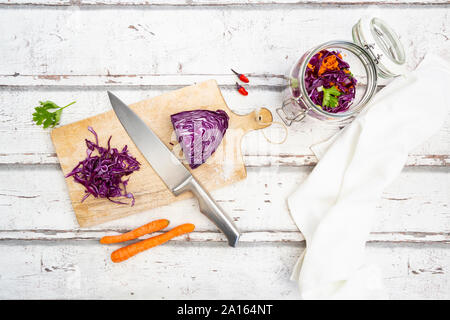 Red cabbage, chili peppers, carrots and coriander on wooden table
