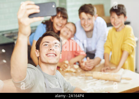 Sone taking pictures of his mother and brothers, preparing pizza at home - Stock Photo