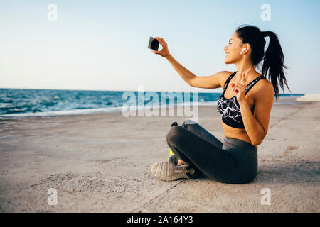 Woman using smartphone and taking a selfie, sitting on a pier