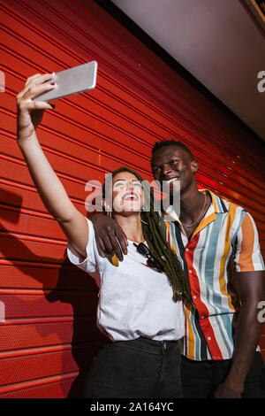 Happy young couple taking a selfie at red roller shutter at night - Stock Photo