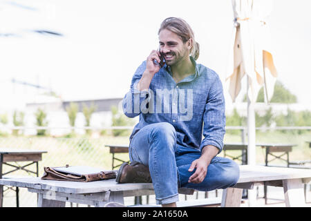 Young man sitting on table in a beer garden talking on the phone - Stock Photo