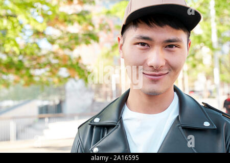 Portrait of confident young man wearing leather jacket and cap, Barcelona, Spain - Stock Photo