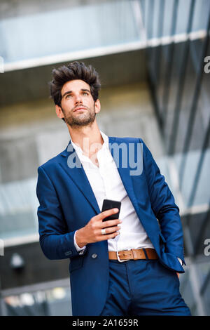 Businessman with cell phone outside an office building - Stock Photo