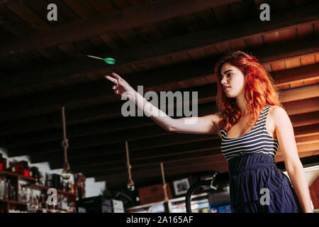 Young woman playing darts in a sports bar - Stock Photo