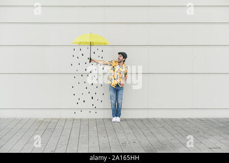 Digital composite of young man holding an umbrella at a wall with raindrops - Stock Photo