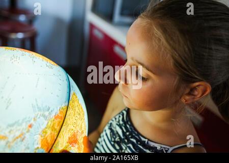 Curious girl looking at illuminated globe - Stock Photo