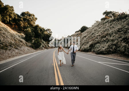 Bride and groom walking hand in hand on a country road - Stock Photo